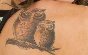 フクロウのタトゥーを肩に入れている女性