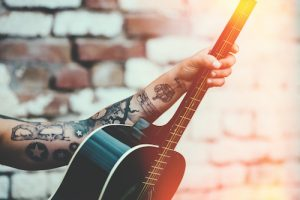 ギターをもつタトゥーの男性