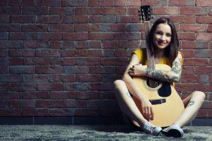 ギターを持つタトゥーの少女