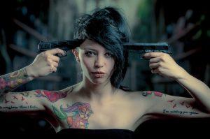 銃とタトゥーの女性